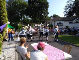 Morris dancers dance in a street party