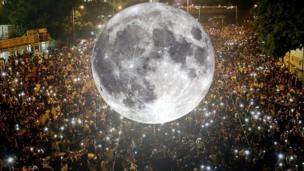 Moon balloon superimposed above a crowd