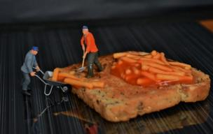 Miniature men move spaghetti on toast.