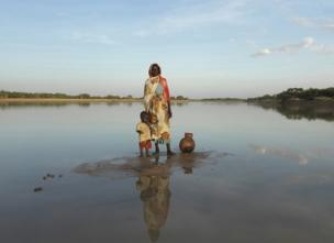 Jumana and her young child collect water