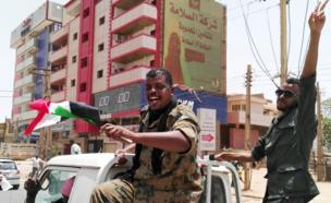 A nan kuma wani soja ne tare da wani farar hula suna nuna murnarsu da labarin hambare Shugaba al-Bashir daga mulki a Sudan.