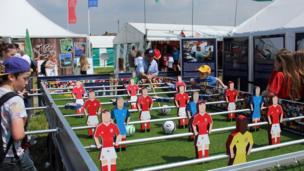 Pobl ifanc yn chwarae pêl-droed bwrdd. // Young people enjoying a game of table football.