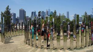 View of the Manhattan skyline and New Yorkers partially hidden by a mirrored sculpture in Brooklyn