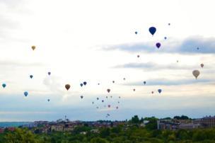 Hot air balloons fly overhead