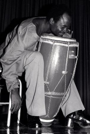 A man leans his chin onto a drum as he plays it, he is elated