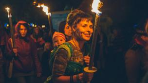 A youngster enjoys the ambience as those in the procession carry torches through Portmeirion Village.