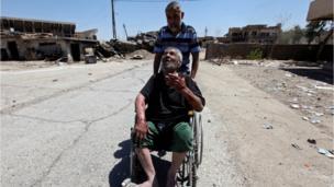 رجل يدفع رجل عجوزا على كرسي متحرك بعد فرارهما من القتال الدائر في مدينة الموصل القديمة يوم السبت 24/ 6 / 2017