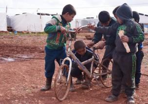 Niños jugando con una bicicleta.