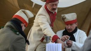 Enthusiasts dressed as soldiers prepare their ammunition