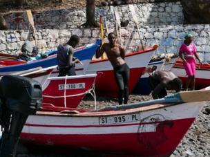 شباب من جزر الرأس الأخضر يقفون إلى جوار مراكب صيد.