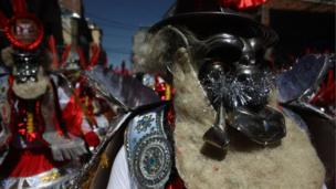 A dancer wears an elaborate mask during the Lord of the Great Power parade in La Paz