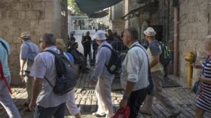 مجموعة من الزائرين للمنطقة يمرون عبر الشرطة الإسرائيلية