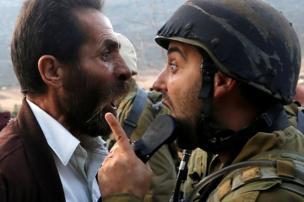 رجل فلسطيني يتجادل مع جندي إسرائيلي