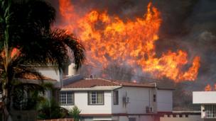 Flames engulf the hillside near a home in southern California.