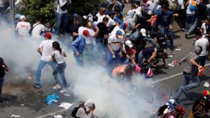 Manifestantes se protegen de los gases