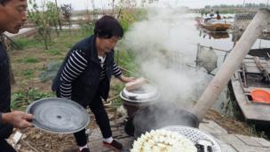 白洋淀的居民为住在家中的游客煮饺子。