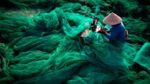 Una mujer sentada frente a su máquina de coser remienda una enorme red de pesca que ocupa el resto de la imagen