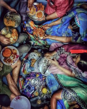 A family feasts on roti, rice and curries on a train.