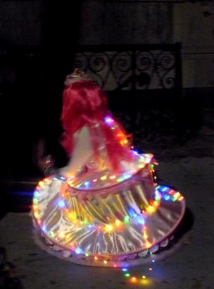 A young girl wearing a light bulb dress with a pink wig, lights up a dark night behind her