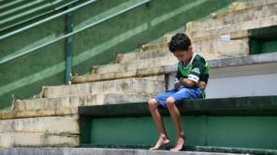 A young boy alone in the stands at Chapecoense Real's stadium in southern Brazil