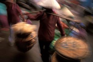 امرأة تحمل بضاعة في سوق