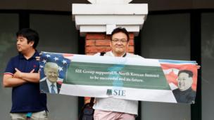 مواطن من كوريا الجنوبية يرفع لافتة دعم للقمة التي جاءت بعد حرب كلامية بين الولايات المتحدة وكوريا الشمالية.