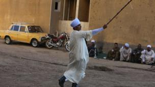 رجل يرقص بالعصا