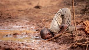Un niño se arrodilla para beber agua sucia en un terreno lleno de lodo en Kamanega, Kenia.