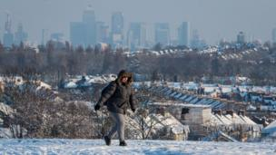 A woman walks over Blythe Hill, in south London