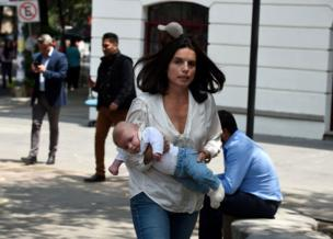 A woman rushes with her baby through the streets after a quake rattled Mexico City on 19 September