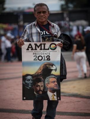 Hombre con una pancarta de AMLO para presidente.