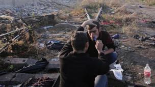 Bir mülteci bir diğerinin sakalını kesiyor.