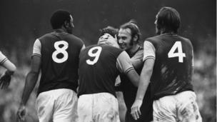 West Ham's Bryan 'Pop' Robson hugs the England hero Geoff Hurst after he equalises in a match against Leicester City at Upton Park