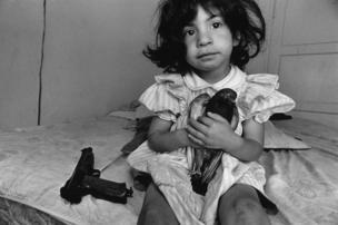 طفلة صغيرة تحتضن حمامة وبجوارها مسدس.