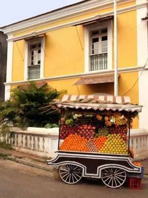 Casa colonial amarela perto de uma carrocinha vendendo mangas