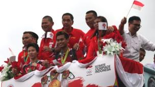 Indonesian badminton players Liliyana Natsir (back, left) and Tantowi Ahmad (back, second left wave from a bus as they parade in Cengkareng, Banten, Indonesia