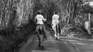 Two horse riders on a country lane