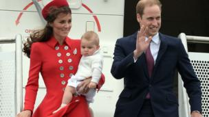 Kate holding George as they exit an aeroplane