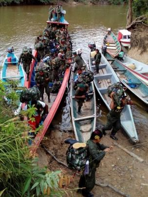 A handout photo provided by the Farc rebels shows them disembarking from a canoe