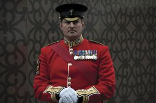 A soldier dressed in a red tunic standing by the roadside watching the funeral cortege for Margaret Thatcher, near Fleet Street, London