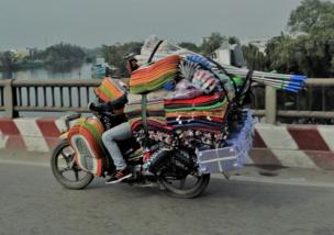 A moped is packed with bath mats, boxes and mops, a driver is crammed in as he drives on
