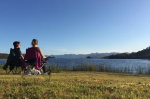 Pareja sentada frente a un lago