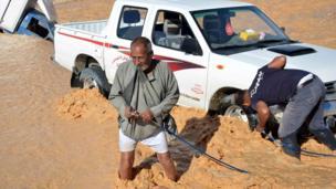 رجل يستخدم حبلا لسحب سيارة انحرفت خارج الطريق جراء الأمطار الغزيرة في محافظة قنا