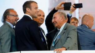 French President Emmanuel Macron (2ndL) listens to Dassault Aviation CEO Eric Trappier (C) and Dassault Chairman Serge Dassault (R) while visiting the Paris Air Show in Le Bourget, north of Paris, on June 19, 2017.