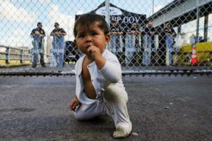 A Mexican one-year-old awaiting her turn to seek asylum in the US with her mother is seen in front of the gates to the Gateway International Bridge in Matamoros.