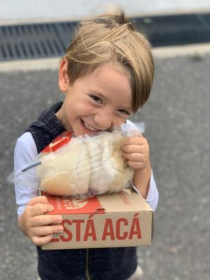 Un niño sostiene una caja con panes.