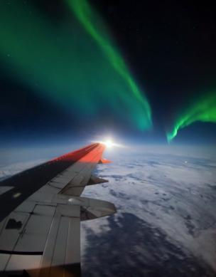 الأضواء الشمالية فوق جناج طائرة بوينغ.