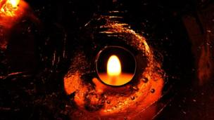 A candle seen through a hole in a sheet of ice