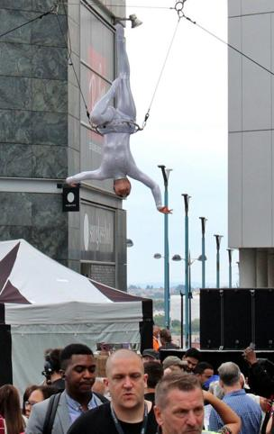 An acrobat is suspended above the street, over peoples heads