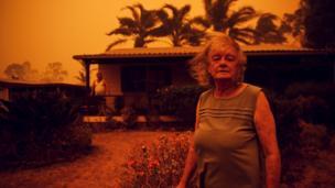 Os moradores Nancy Allen e Brian Allen, de Nova Gales do Sul, permancem do lado de fora da casa enquanto ventos fortes empurram fumaça e cinzas